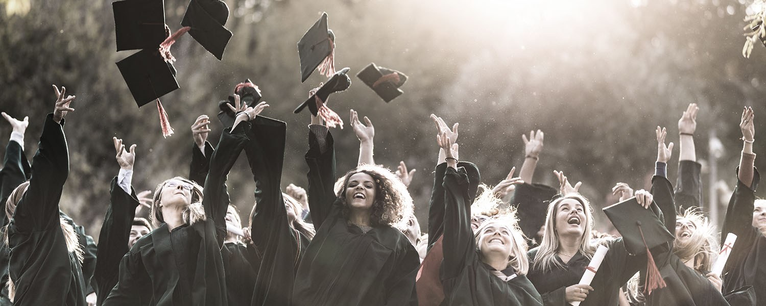 Large group of happy college students celebrating their graduation day outdoors while throwing their caps up in the air.